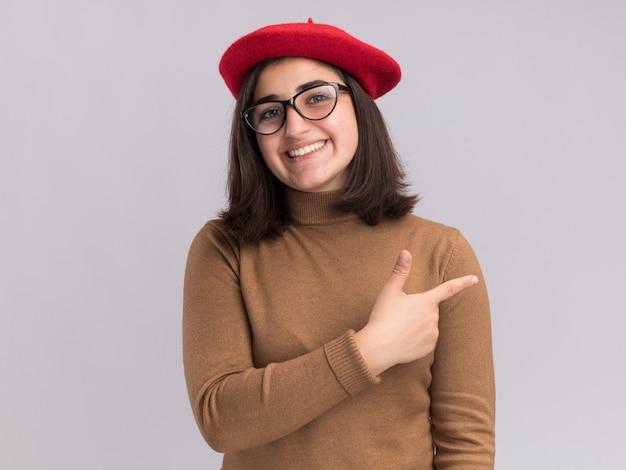ベレー帽の帽子とコピースペースで白い壁に隔離された側を指している光学メガネで笑顔の若いかなり白人の女の子