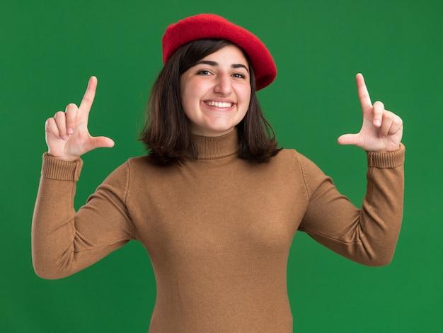 コピースペースと緑の壁に分離された手でフレームを身振りで示すベレー帽の帽子を持つ若いかなり白人の女の子の笑顔
