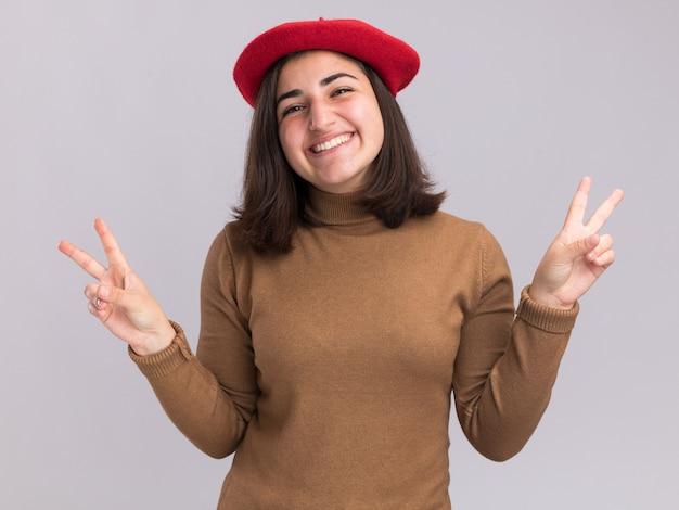 コピースペースと白い壁に分離された両手で勝利のサインを身振りで示すベレー帽の帽子と笑顔の若いかなり白人の女の子