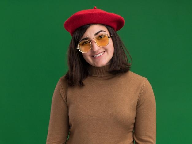 コピースペースと緑の壁に分離されたサングラスでベレー帽の帽子と笑顔の若いかなり白人の女の子