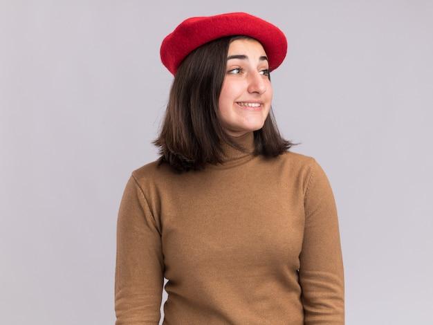 コピースペースで白い壁に分離された側を見てベレー帽の帽子と笑顔の若いかなり白人の女の子 無料写真