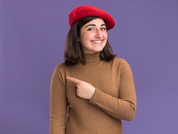 コピースペースと紫色の壁に分離された側を指しているベレー帽の帽子と笑顔の若いかなり白人の女の子