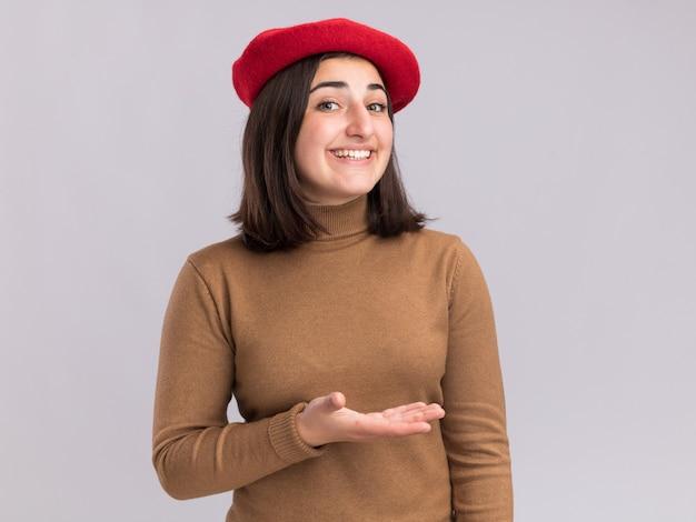 Sorridente giovane bella ragazza caucasica con cappello berretto che punta a lato con la mano isolata sul muro bianco con spazio copia