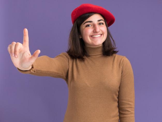 コピースペースと紫色の壁に分離された上向きのベレー帽の帽子と笑顔の若いかなり白人の女の子