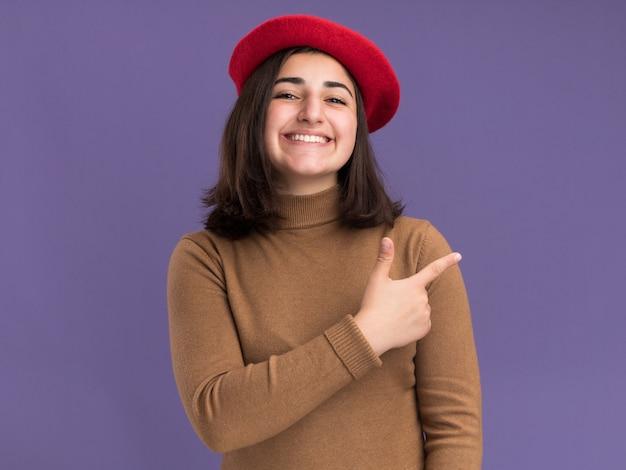 コピースペースと紫色の壁に分離された側にベレー帽の帽子のポイントを持つ若いかなり白人の女の子の笑顔