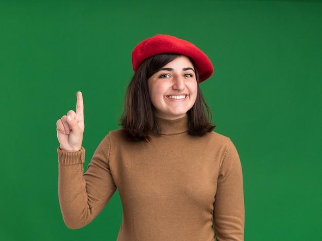Улыбающаяся молодая симпатичная кавказская девушка в берете указывает вверх