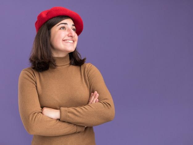 コピースペースと紫色の壁で隔離された側を見て交差した腕で立っているベレー帽の帽子を持つ若いかなり白人の女の子の笑顔