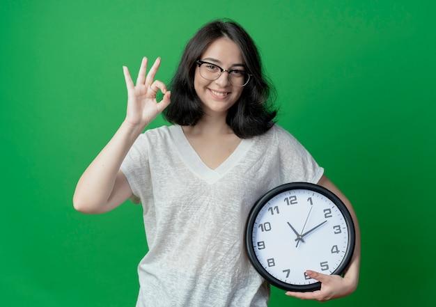 Sorridente giovane donna piuttosto indoeuropea tenendo l'orologio e facendo segno ok isolato sul verde