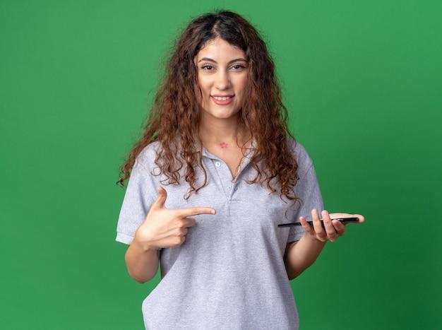 Sorridente giovane donna abbastanza caucasica che tiene e indica il telefono cellulare
