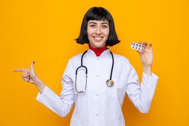 Улыбающаяся молодая симпатичная кавказская женщина в униформе врача со стетоскопом, держащая упаковку таблеток и указывая в сторону