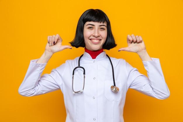 두 손으로 자신을 가리키는 청진기를 들고 의사복을 입은 젊은 백인 여성