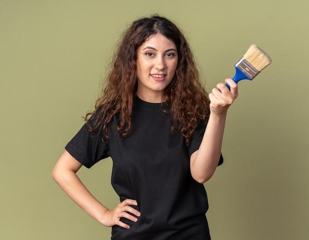 Sorridente giovane donna abbastanza caucasica che tiene la mano sulla vita tenendo il pennello