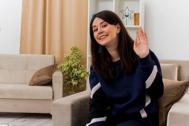 Улыбающаяся молодая симпатичная кавказская женщина, сидящая на кресле в дизайнерской гостиной, делает приветственный жест