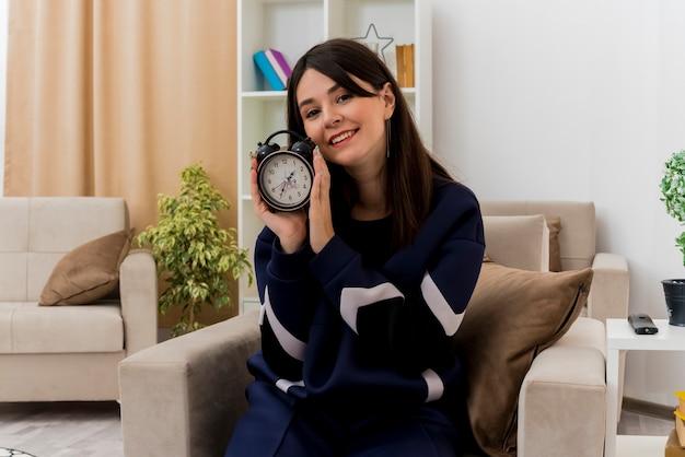 알람 시계를 들고 설계 거실에서 안락의 자에 앉아 웃는 젊은 예쁜 백인 여자