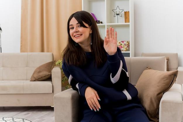 디자인 된 거실에서 안락의 자에 앉아 찾고 빈 손을 보여주는 웃는 젊은 예쁜 백인 여자