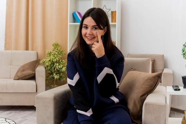 Улыбающаяся молодая симпатичная кавказская женщина, сидящая на кресле в дизайнерской гостиной, смотрит, положив палец под глаз