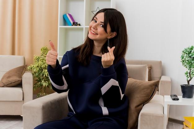 Улыбающаяся молодая симпатичная кавказская женщина, сидящая на кресле в дизайнерской гостиной, смотрит вверх и делает денежный жест