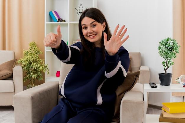 손으로 여섯을 보여주는 설계 거실에서 안락의 자에 앉아 웃는 젊은 예쁜 백인 여자