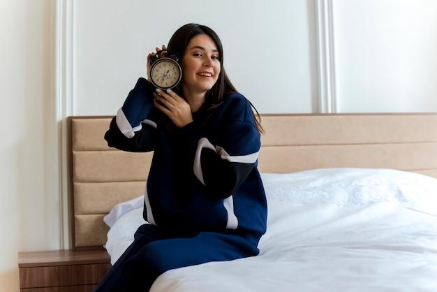 頭の近くで目覚まし時計を保持している寝室のベッドに座っている若いかなり白人女性の笑顔