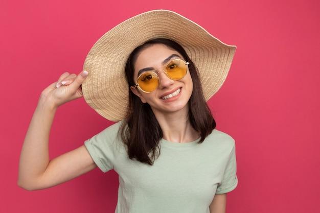 Sorridente giovane bella donna caucasica che indossa cappello da spiaggia e occhiali da sole che afferra il cappello