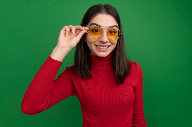 Sorridente giovane bella donna caucasica che indossa e afferra gli occhiali da sole