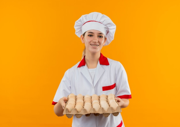 Sorridente giovane cuoco grazioso in uniforme da chef con parentesi graffe dentali che tiene il cartone di uova isolato su spazio arancione