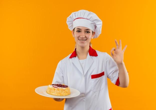 Sorridente giovane cuoco grazioso in uniforme da chef con bretelle dentali che tiene piatto di torta e facendo segno giusto isolato su spazio arancione