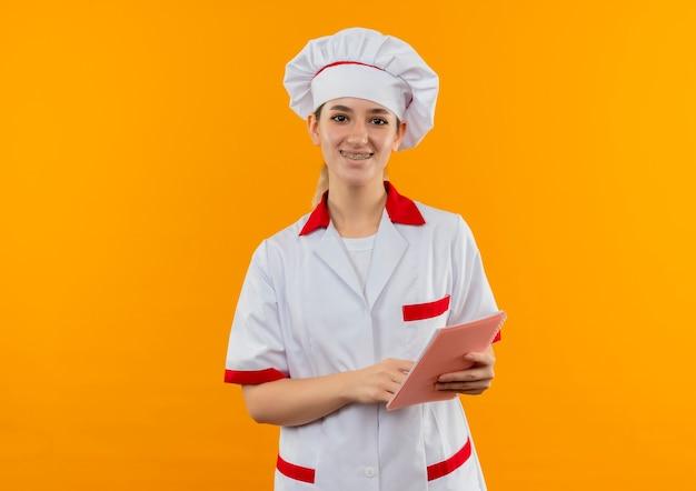 Sorridente giovane cuoco grazioso in uniforme da chef con parentesi graffe dentali tenendo e mettendo il dito sul blocco note isolato su spazio arancione