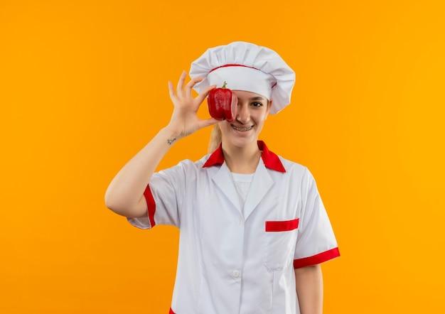 Sorridente giovane cuoco grazioso in uniforme del cuoco unico con le parentesi graffe dentali che mettono pepe sull'occhio isolato sullo spazio arancione