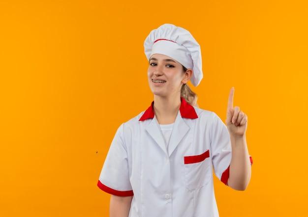 Улыбающийся молодой симпатичный повар в униформе шеф-повара, поднимающий палец на оранжевом пространстве