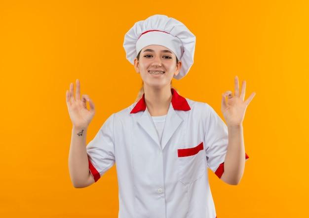 Улыбающийся молодой симпатичный повар в униформе шеф-повара с зубными скобами делает знаки ок, изолированные на оранжевом пространстве
