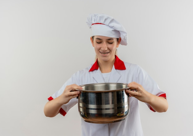 Улыбающийся молодой симпатичный повар в униформе шеф-повара с зубными скобами, держащий и смотрящий на горшок, изолированный на белом пространстве