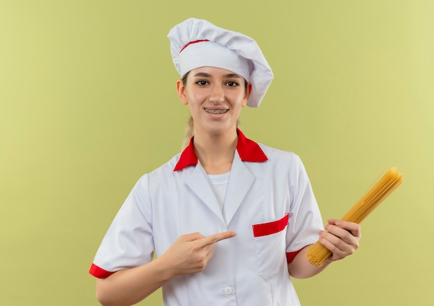 Улыбающийся молодой симпатичный повар в униформе шеф-повара с зубными скобами, держащий и указывающий на спагетти, изолированные на зеленом пространстве