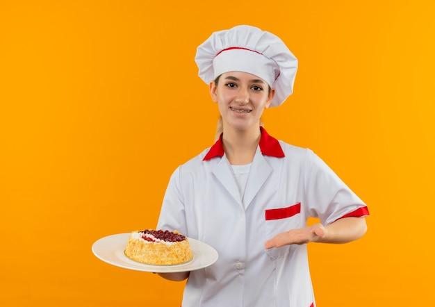 Улыбающийся молодой симпатичный повар в форме шеф-повара с зубными скобами, держащий и указывающий рукой на тарелку торта, изолированную на оранжевом пространстве