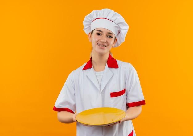 Улыбающийся молодой симпатичный повар в униформе шеф-повара с зубными скобами держит пустую тарелку, изолированную на оранжевом пространстве