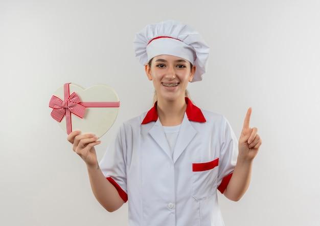 ハート型のギフトボックスを保持し、白いスペースで隔離された指を上げる歯列矯正器でシェフの制服を着た若いかわいい料理人の笑顔