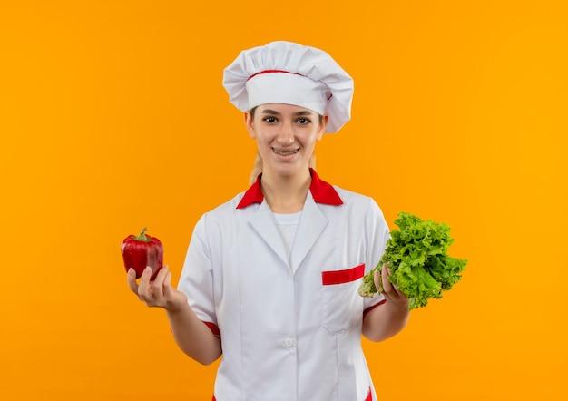 Улыбающийся молодой симпатичный повар в униформе шеф-повара с зубными скобами, держащий перец и салат, изолированные на оранжевом пространстве