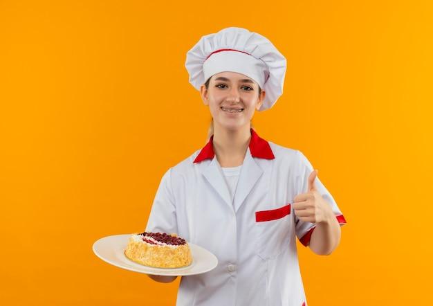Улыбающийся молодой симпатичный повар в униформе шеф-повара с зубными скобами держит тарелку торта и показывает большой палец вверх изолированным на оранжевом пространстве