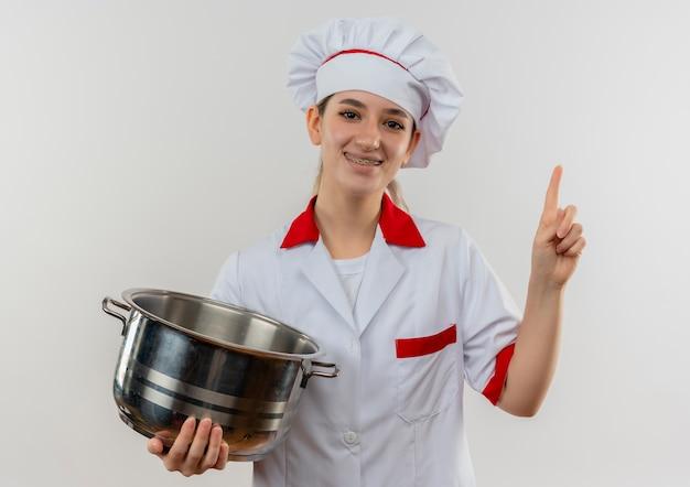Улыбающийся молодой симпатичный повар в униформе шеф-повара с зубными скобами, держащий горшок и поднимающий палец, изолированный на белом пространстве
