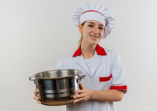 白いスペースに孤立して見える鍋を保持している歯科用ブレースとシェフの制服を着た若いかわいい料理人の笑顔