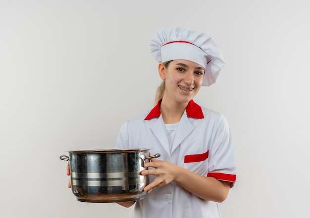 Улыбающийся молодой симпатичный повар в форме шеф-повара с зубными скобами, держащий горшок, выглядит изолированным на белом пространстве
