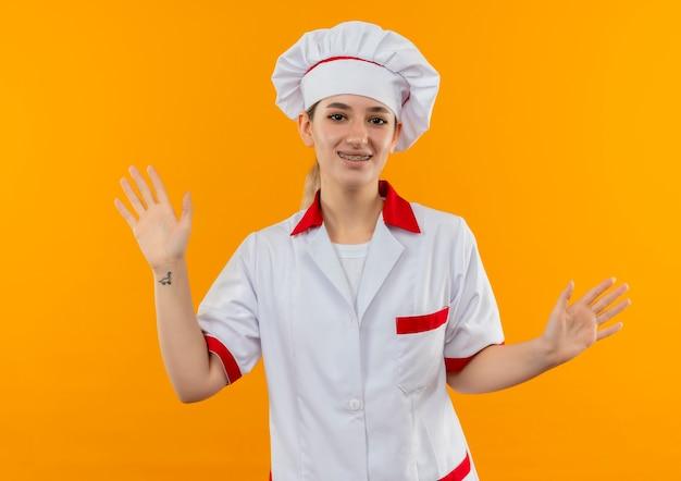 オレンジ色のスペースで隔離された空の手を示す歯科用ブレースとシェフの制服を着た若いかわいい料理人の笑顔