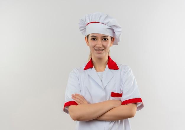 白いスペースで隔離の閉じた姿勢で立っている歯科用ブレースとシェフの制服で若いかわいい料理人の笑顔