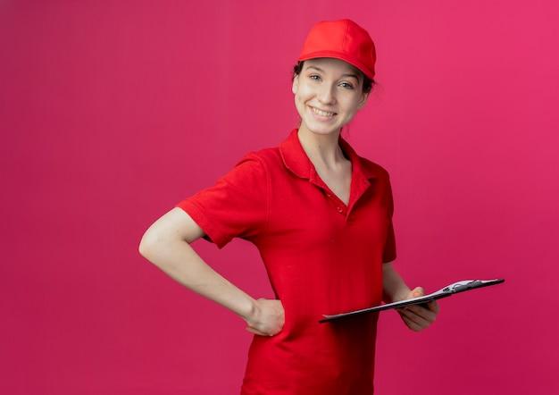 赤い制服とコピースペースで深紅色の背景に分離された腰に手を置くクリップボードを保持している帽子の若いかわいい配達の女の子の笑顔