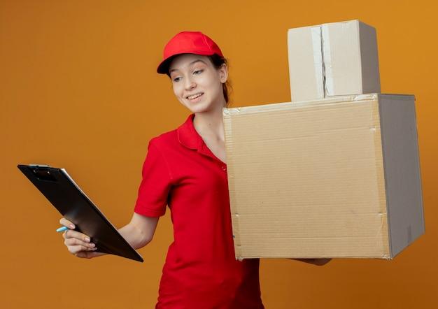 Улыбающаяся молодая симпатичная доставщица в красной форме и кепке, держащая ручку и буфер обмена, смотрит в буфер обмена с картонными коробками в другой руке, изолированной на оранжевом фоне