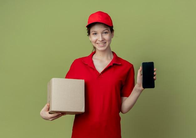 Улыбающаяся молодая симпатичная курьерская девушка в красной форме и кепке показывает мобильный телефон и держит картонную коробку, изолированную на оливково-зеленом фоне