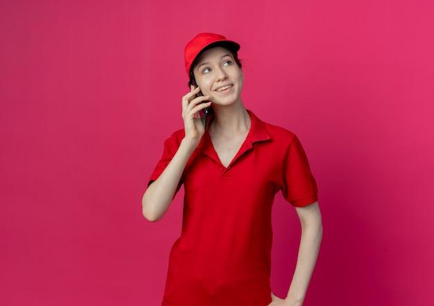 Улыбающаяся молодая симпатичная доставщица в красной форме и кепке разговаривает по телефону, глядя в сторону, изолированную на малиновом фоне с копией пространства