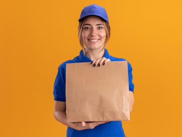 Улыбающаяся молодая симпатичная курьерская девушка в униформе, держащая бумажный пакет на оранжевом