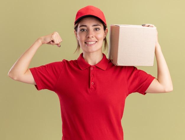 制服を着た笑顔の若いかわいい配達の女の子は、カードボックスを保持し、オリーブグリーンの上腕二頭筋を緊張させます