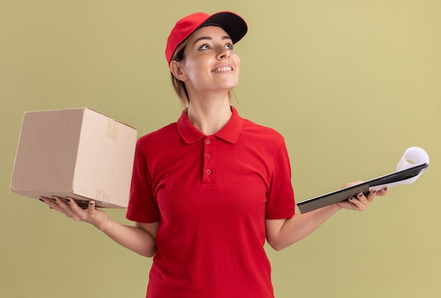 제복을 입은 젊은 예쁜 배달 소녀 미소는 올리브 그린에 측면을보고 클립 보드와 cardbox를 보유하고